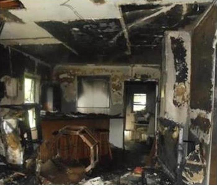 A living room covered in smoke and soot damage from a fire