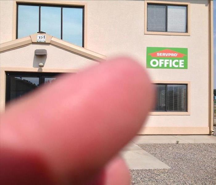 Thumb in photo pointing to SERVPRO Signage at Facility